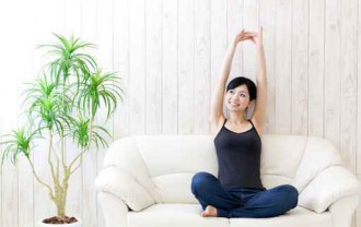 a young asian woman stretching on the sofa