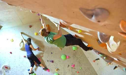 Frau und Mann bouldern in einer Kletterhalle