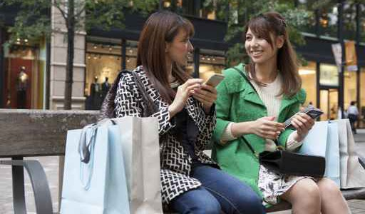 Two women are talking and sitting on a bench