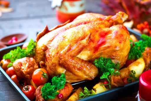 Roasted turkey garnished with potato, vegetables and cranberries