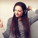Young beautiful woman listening the music from headphones with d