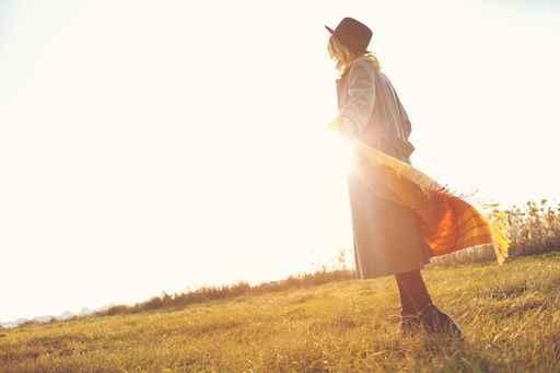 Romantic girl walking in a field in sunset light. Winter, autumn