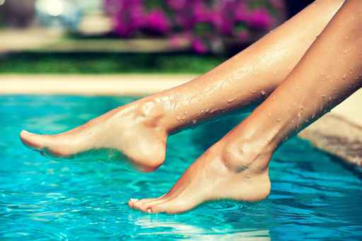 Slender female legs splash in the water . Well-groomed girlish l