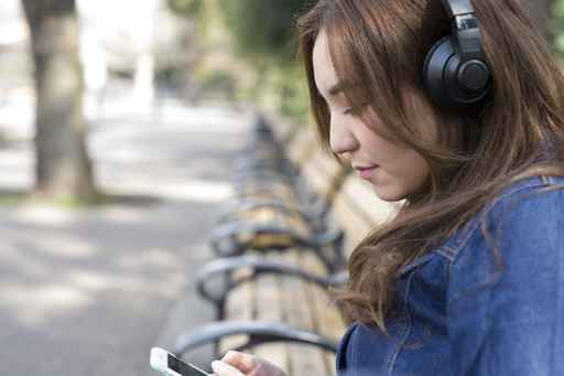 Young woman wearing a headphone is sitting on a bench in the par