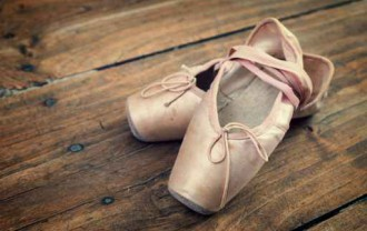 Old pink ballet shoes on a wooden floor, vintage process