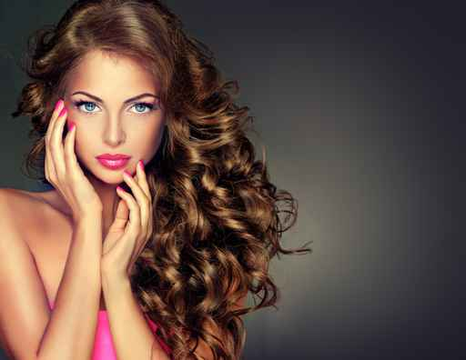 Beautiful model brunette with long curled hair . Hairstyle wavy