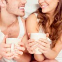 Cute young couple sitting together with cups and smiling