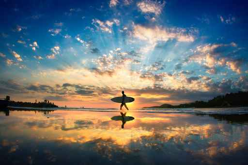 Sun surfer. A man is walking with a surf in his hands across the