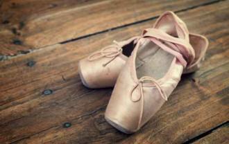 Old pink ballet shoes on a wooden floor, vintage process
